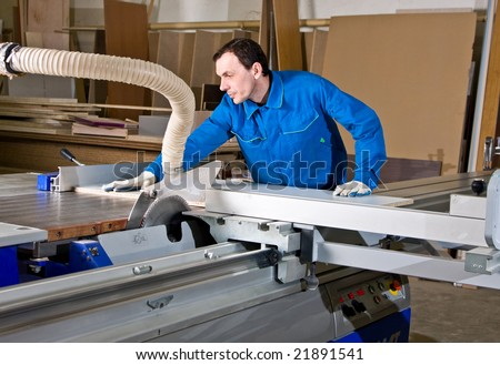 The man the worker, works on the machine tool and saws wooden products - stock photo