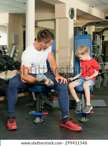 The man trains a young boy in the gym with exercise equipment - stock photo