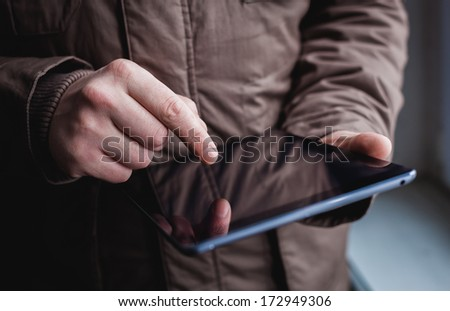 The man uses a tablet PC. Modern gadget in hand.