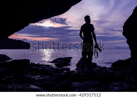 The man with camera stay in front of the cave near the sea with purple sky in the morning.