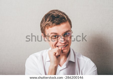 The man with glasses biting his fists, bites his nails. On a gray background. - stock photo