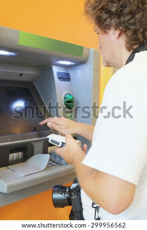 The man withdraws money from the ATM