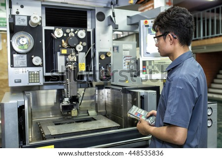 The man working control with cnc wire cut at workshop. - stock photo
