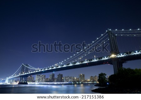 The Manhattan Bridge is a suspension bridge that crosses the East River in New York City, connecting Lower Manhattan with Brooklyn. - stock photo