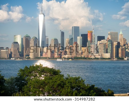 The Manhattan skyline as seen from Ellis Island with the ocean illuminated by light coming from One World Trade Center - stock photo
