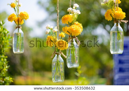 The marigold flowers in a glass bottle hanging. Flower vase arrangements - stock photo