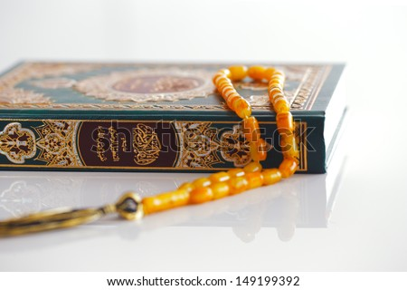 The Masbaha is also known as Tasbih is a string of prayer beads which is traditionally used by Muslims to keep track of counting in tasbih - seen here with the Quaran - stock photo