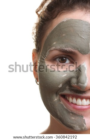 the mask of healing clay on the face of woman on white isolated background