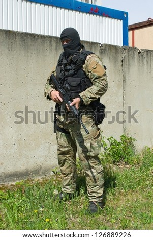 The masked man pointing a weapon - stock photo