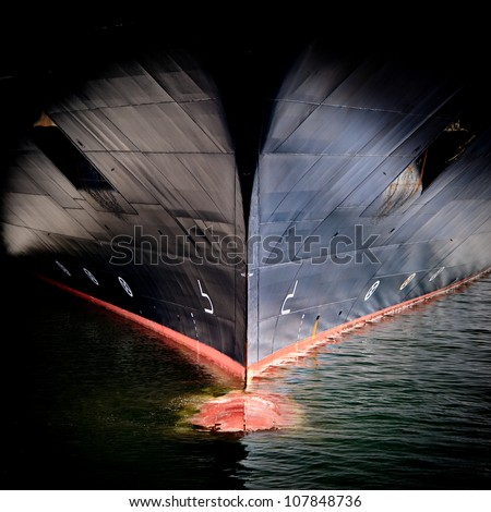 The massive bow of a large ship, with the radar dome cresting the surface of the water. - stock photo