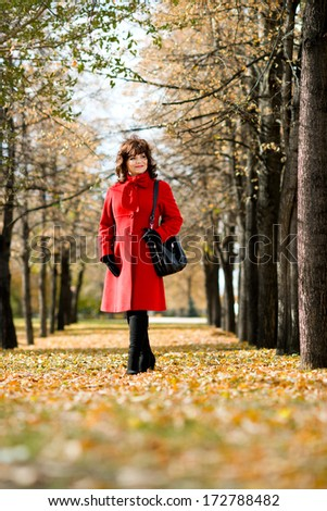The  mature beautiful woman in red topcoat,  outdoor in park, autumnal day
