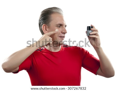 The mature man applies the cream which is looking after face skin