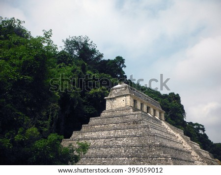 The Mayan Temple of Inscriptions at the Palenque archeological site in Chiapas, Mexico, backed by dense jungle.