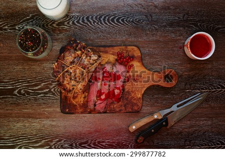 The meat medium rare with blood, lying on a wooden board where the cook cut it into pieces a la carte, served with meat is cooked vegetables on the grill - stock photo