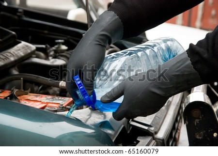 The mechanic fills washing liquid to the car