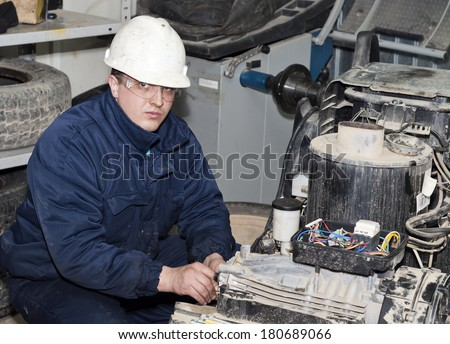 the mechanic serves the production equipment. - stock photo