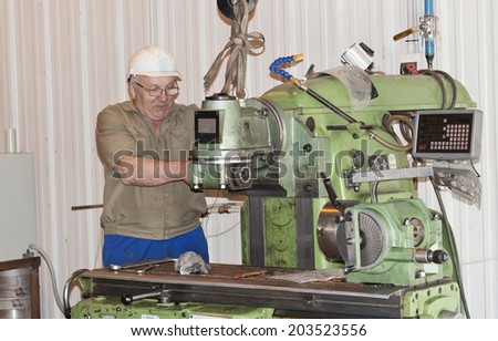 The mechanic works at the milling machine - stock photo