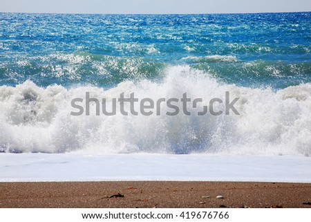 The Mediterranean Sea with large waves and surf, seen from a shoreline beach in Cyprus - stock photo