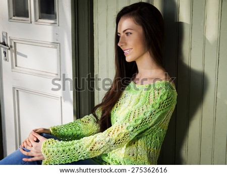 The menthol girl in a knitted sweater, has a rest in the evening