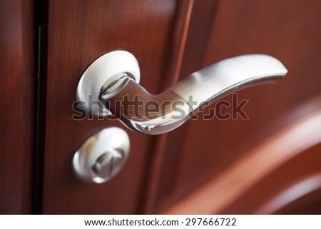 The metal door handle on a brown door close up. - stock photo