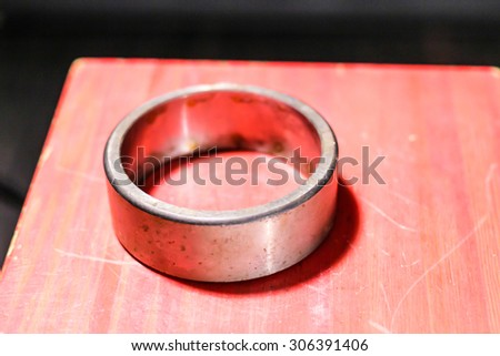 The metal ring on a red wooden background - stock photo