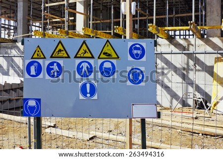 The metal stand with the standard warning signs of labor protection and health on building - stock photo