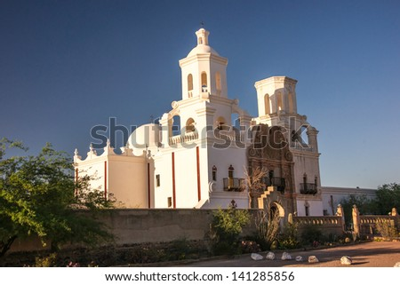 The meticulously restored mission of San Xavier stands in contrast with the deep blue sky. - stock photo