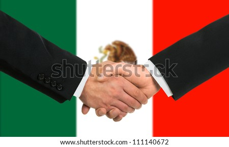The Mexican flag and business handshake - stock photo