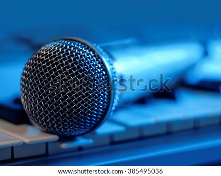 The microphone on the keyboard in blue light - low key, partly out of focus, focus on the microphone head       - stock photo