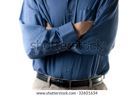The mid section of a man wearing a dress shirt and khaki pants with a black belt, hands crossed. - stock photo