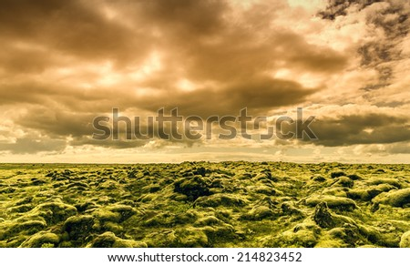 The midnight sun above moss covered lava rocks in south Iceland - stock photo