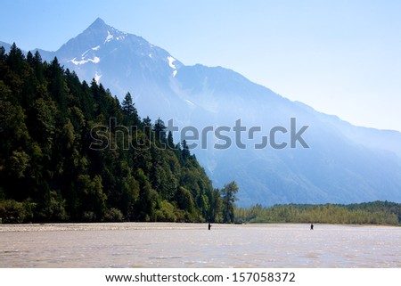 The mighty Fraser River with large mountain in the background in British Columbia Canada - stock photo