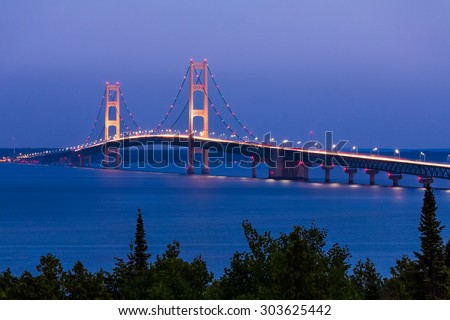 The Mighty Mackinac Bridge, connecting Michigan's Upper and Lower Peninsulas, carries vehicles over waters flowing from Lake Michigan and into Lake Huron. - stock photo