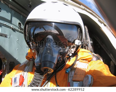 The military pilot in the plane in a helmet in dark blue overalls against the blue sky - stock photo