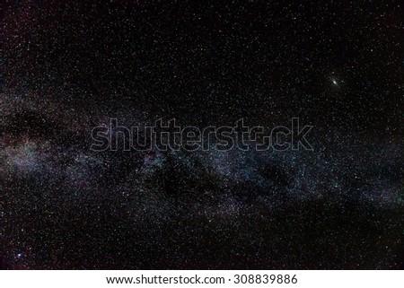 The Milky Way, accompanied by M51 Andromeda Galaxy - stock photo