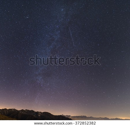 The Milky Way and the starry sky from high up on the Alps with scenic mountain landscape. Andromeda galaxy on the upper left quadrant, an artificial satellite contrail in the center. - stock photo