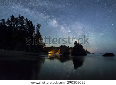 The Milky Way lights up the southern sky while a campfire illuminated the seas stacks on Ruby Beach in Olympic National Park, Washington. - stock photo