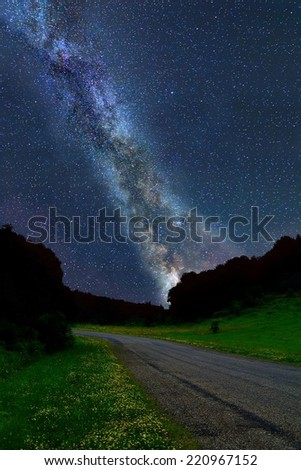 The Milky Way over a country road with green grass and wildflowers in the foreground. - stock photo