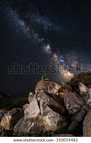 The milky way over a lonely man on rocks admiring it. - it all in focus and the noise is very low for this type of picture. - stock photo