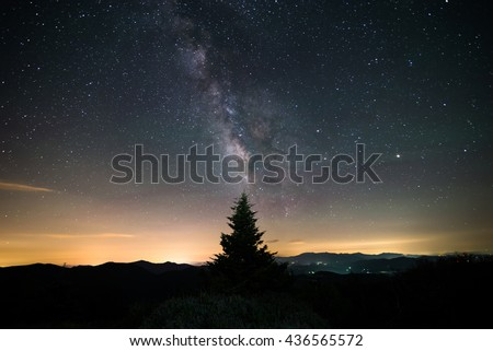 The milky way over the Blue Ridge Mountains on the border of North Carolina and Tennessee along the Appalachian Trail on Round Bald at the Roan Highlands. A Frasier Fir tree sits in the distance.  - stock photo