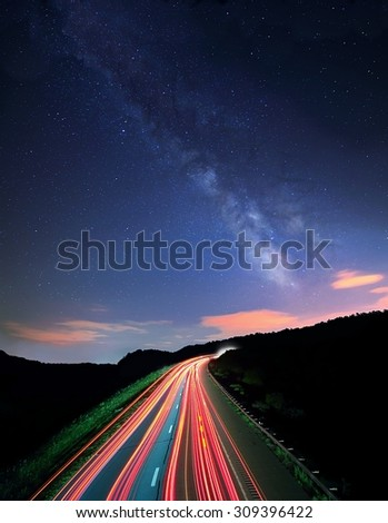 The Milky Way over the westbound lanes of I70 Ohio shot at a slow shutter speed, making the traffic to appear as streaks of light. - stock photo