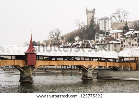The mill bridge (Spreuerbr�¼cke ) covered by snow, with the city wall tower on the background, Lucerne, Switzerland - stock photo