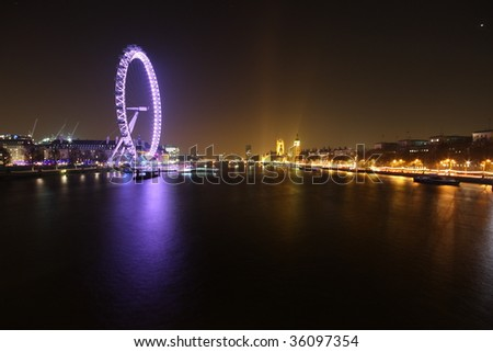 The Millennium Wheel and Houses of Parliament shot at night with a long exposure - stock photo