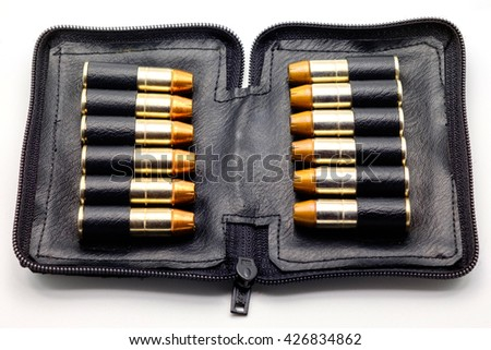The .38 mm bullet for a gun in a black leather pocket on white background. - stock photo