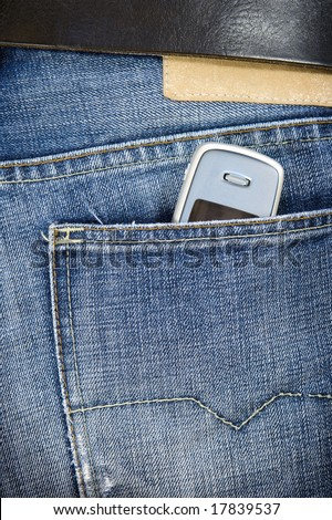 The mobile phone sticks out of a back pocket jeans