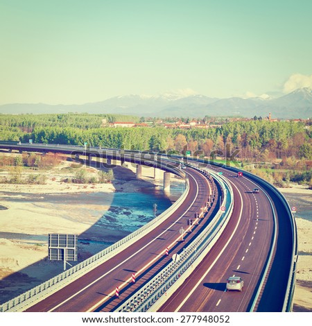 The Modern Highway in Piedmont on the Background of Snow-capped Alps in Italy, Instagram Effect - stock photo