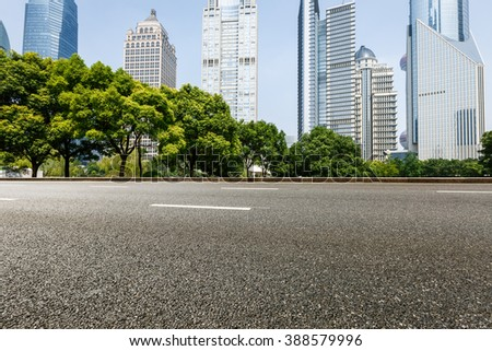 The modern urban commercial building and asphalt road - stock photo