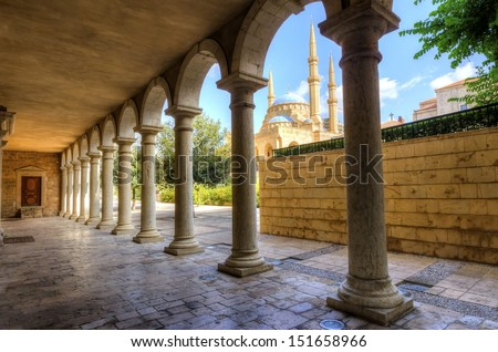 The Mohammad Al-Amin Mosque situated in Downtown Beirut, in Lebanon as viewed through the pillars of the Greek Orthodox church of St George. - stock photo