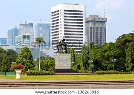 The Monas national monument gardens at Merdeka Square and Jakarta skyline - stock photo