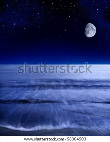 The moon glowing over a calm Pacific ocean shortly after sunset. - stock photo